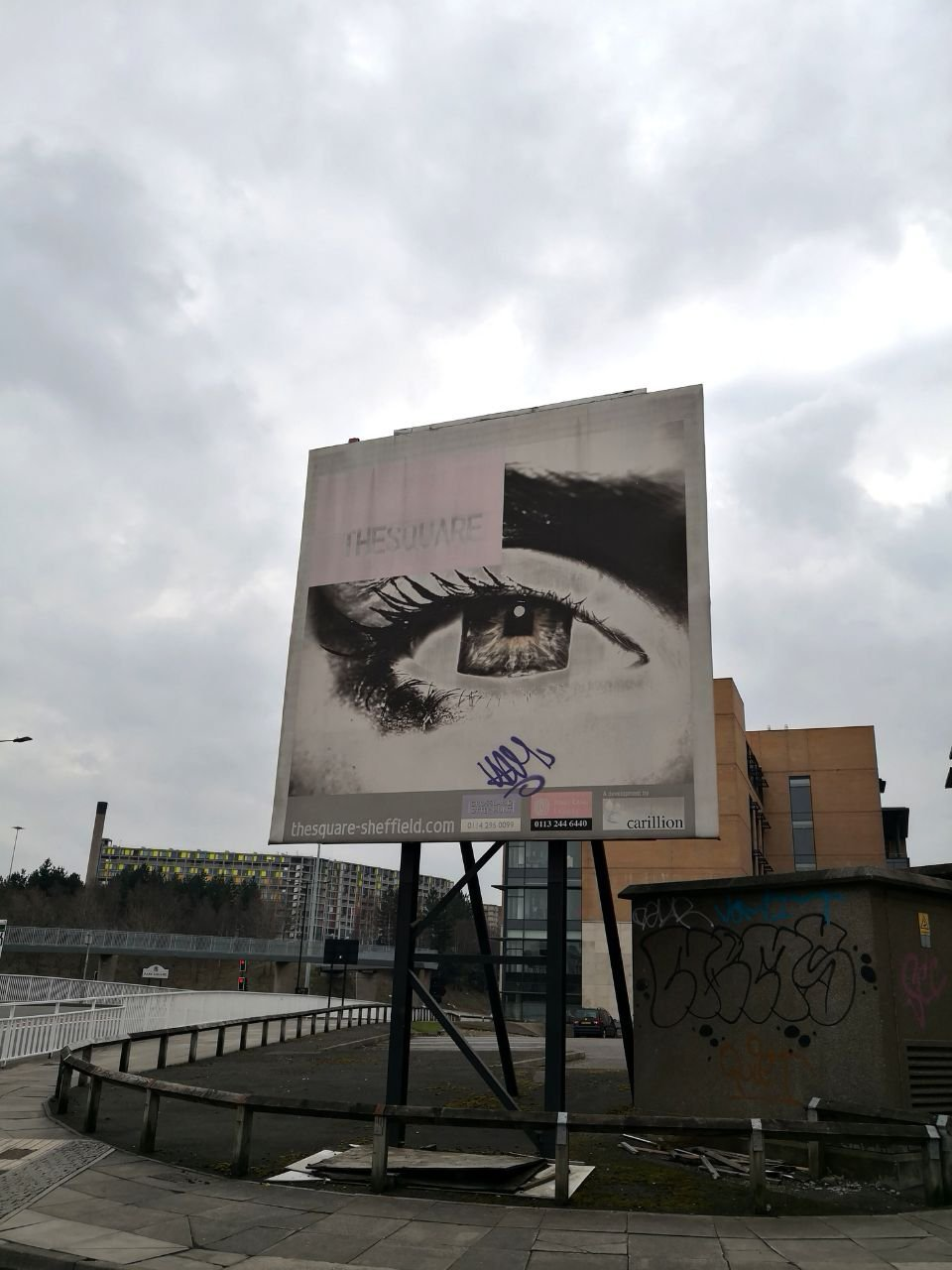 A billboard showing an illustration of a large eye. In the background, an industrial area and cloudy sky.
